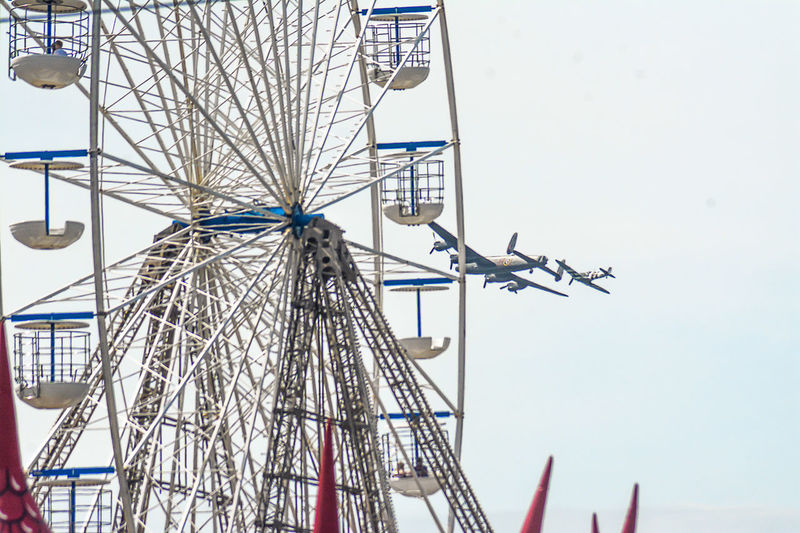 Low angle view of airplanes flying by ferris wheel against clear sky
