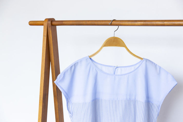Woman blouse with blue blouse cotton on wooden hangers. Coathanger Hanging Clothing No People White Background Studio Shot Indoors  Blue Textile Absence Wood - Material Still Life Fashion Casual Clothing Cut Out Close-up Group Of Objects Three Objects Focus On Foreground White Color Menswear Garment Blue Blouse Cotton Blouse Beige