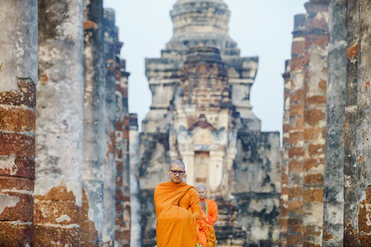 Monks wearing traditional clothing standing in row at temple