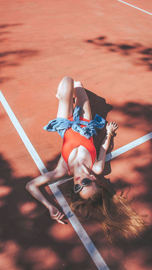 High angle view of woman lying on running track