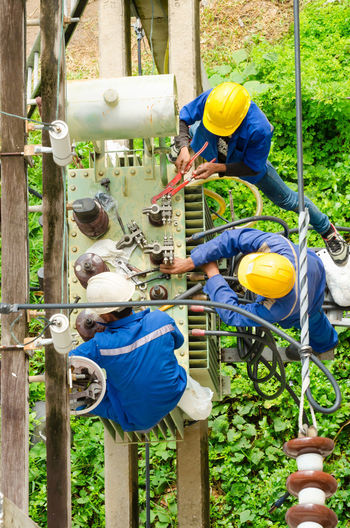 Business Stories Insulator Power Transformer Cable Dangerous Jobs Day Electrician  Electrician, Energy, Engineer, Equipment, Maintenance Work Men Oil Change Outdoors Pole Safety Helmet Teamwork Wires And Cables Wrench