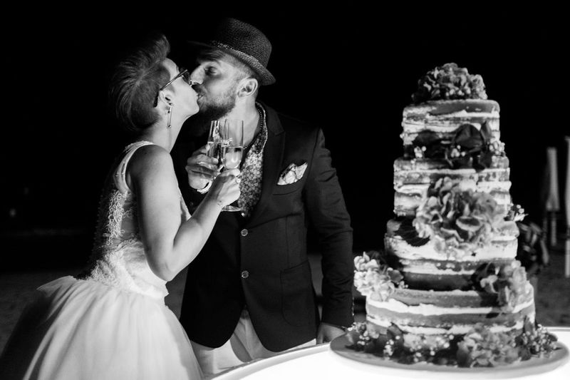 Romantic Newlywed Couple Kissing By Cake