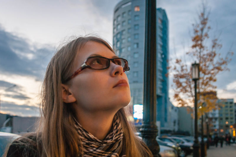 Portrait of young woman looking at city