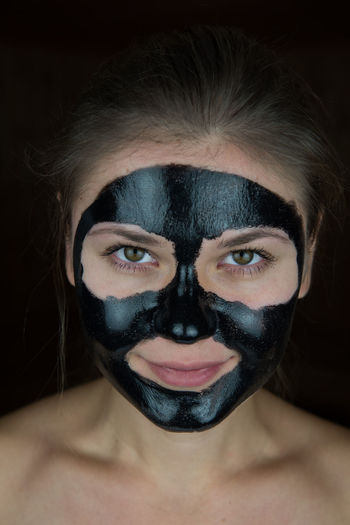 Close-Up Portrait Of Young Woman With Facial Mask Against Black Background