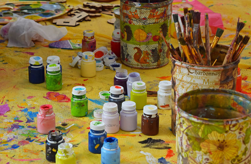 Close-Up Of Paint Bottles And Brushes On Table