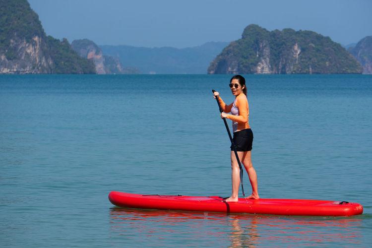 Full length of senior man in sea against mountains