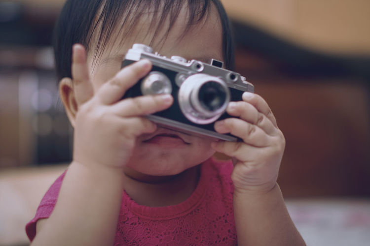Close-up of cute baby girl photographing with camera at home
