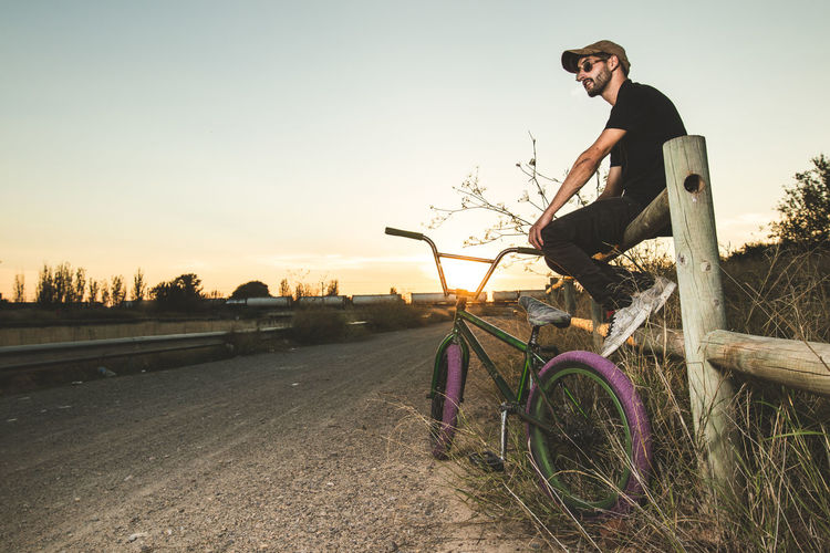 Young man riding bicycle on plants against sky during sunset