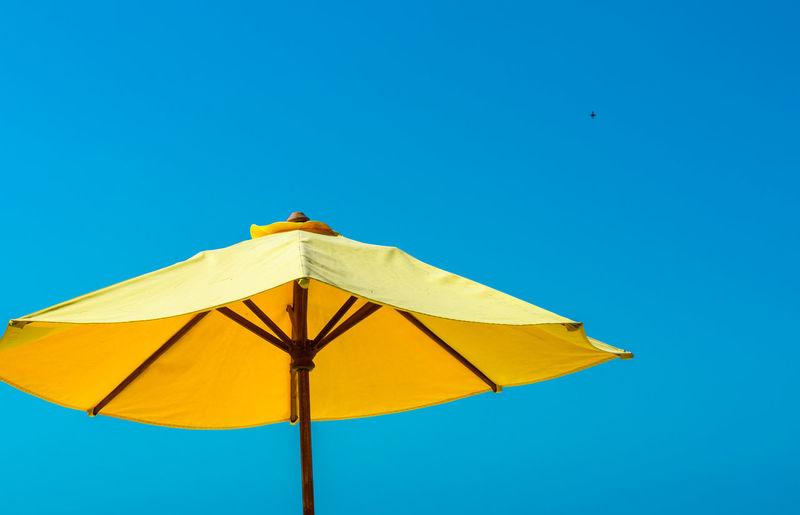 Low angle view of umbrella against blue sky