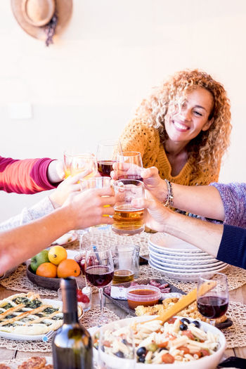 Friend at home or restaurant enjoying and celebrating together clinking and toasting with beers - table full of food and cheerful happy people having fun Food And Drink Smiling Drink Food Refreshment Women Happiness Alcohol Adult Lifestyles Table Two People Togetherness Young Adult Young Women Friendship Glass Sitting Wine Indoors  Hair Meal Hairstyle Group Of People Celebrating Clinking Enjoying A Meal Curly Hair Caucasian Friends Family Restaurant Vacations