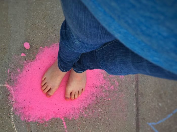 Low Section Of Woman Standing On Pink Chalk Art On Street
