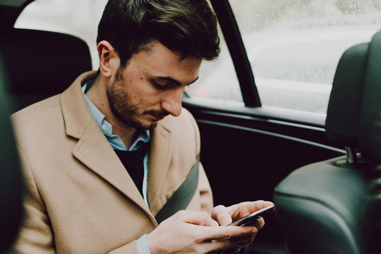 Close-Up Of Businessman Using Phone While Traveling In Car