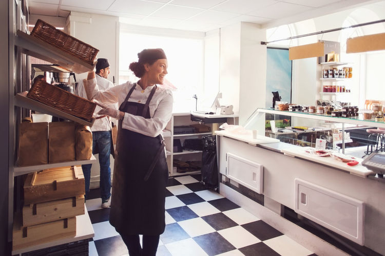 Full length of woman standing in front of kitchen at home