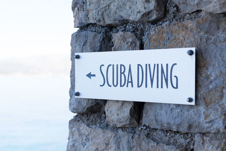 scuba diving metal sign Adventure Background Beach Building Close Up Close-up Coast Detail Diver Extreme Sports Fun Holiday House No People Outdoors Scuba Diving Sea Sign Stone Summer Tile Travel Tropical Vacation Wall