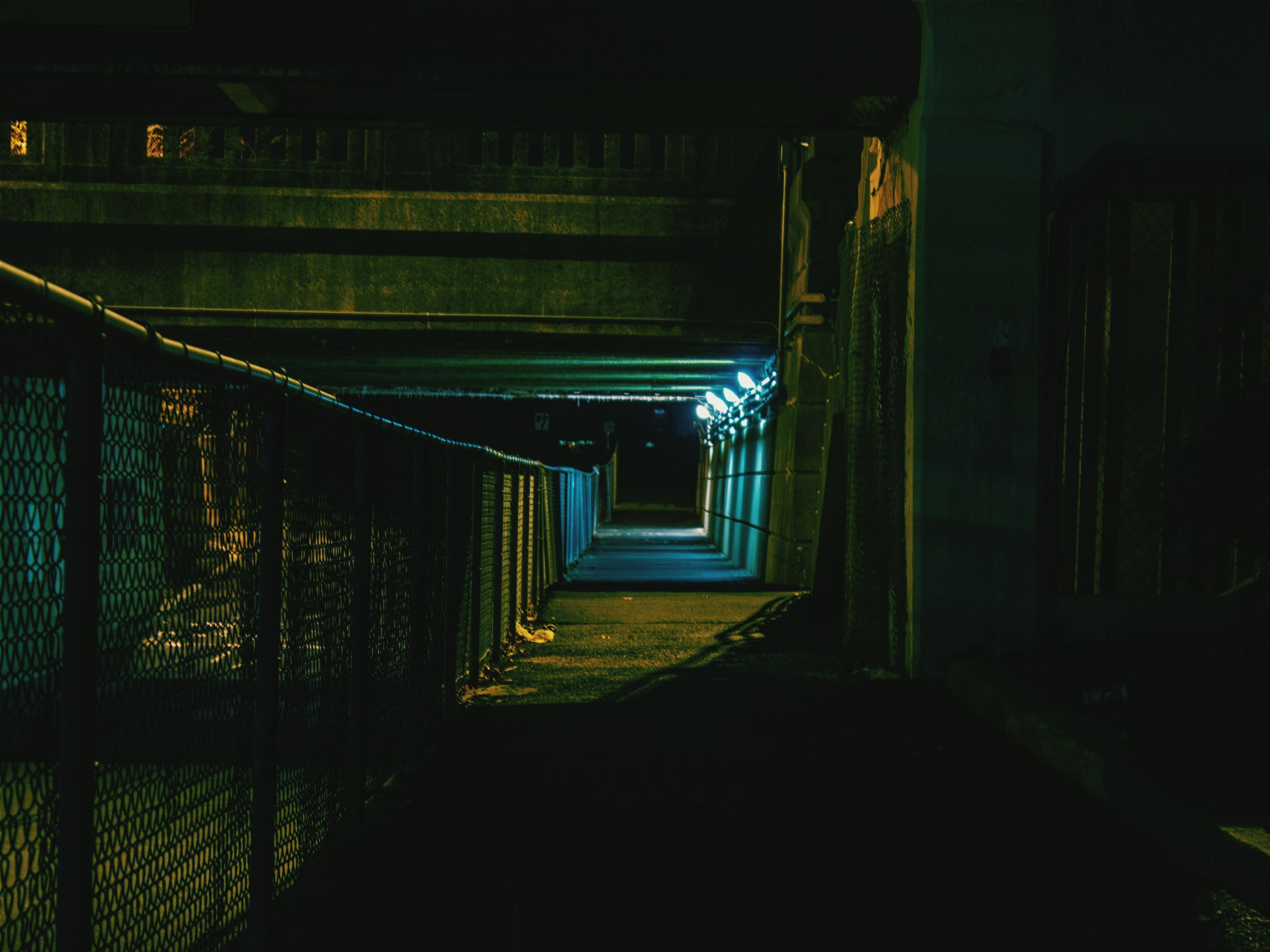 indoors, built structure, architecture, the way forward, illuminated, night, empty, wall - building feature, corridor, dark, steps, door, tunnel, narrow, absence, diminishing perspective, abandoned, no people, building, staircase