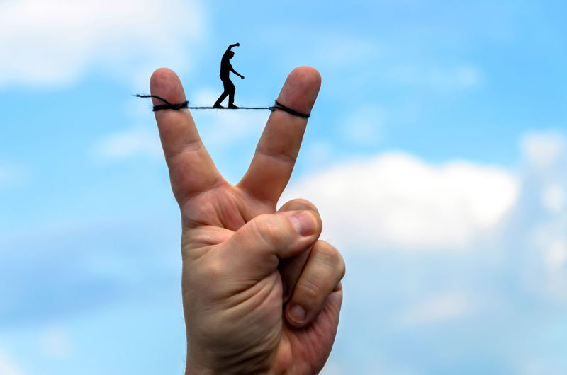 Cropped hand gesturing with creative art against sky