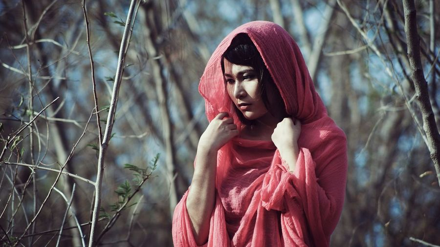 Thoughtful young woman wearing headscarf standing in forest