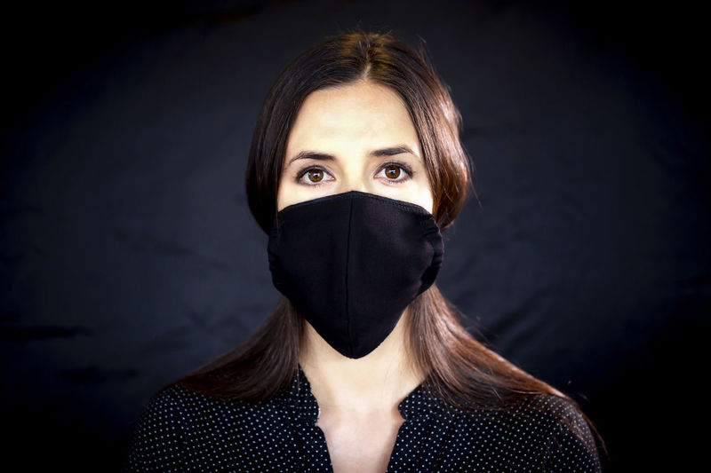 Portrait of woman covering face against black background