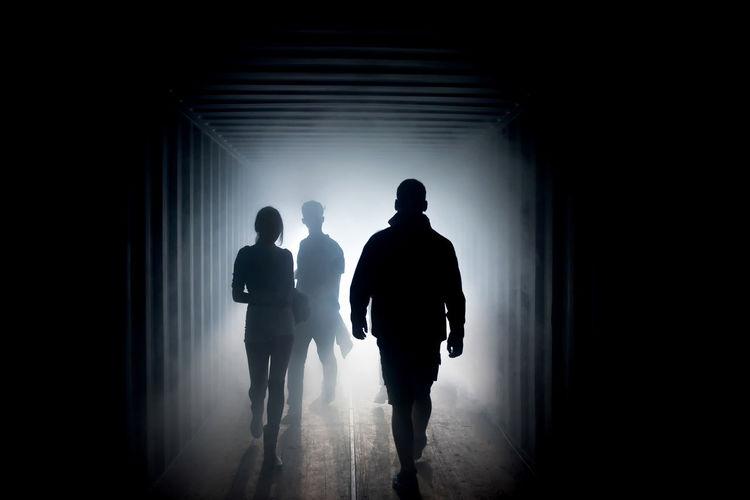 Rear view of silhouette people walking in tunnel
