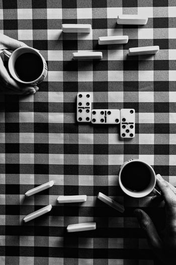 High angle view of hands with coffee in cup on table
