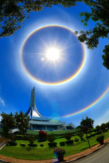 Halo around sun with blue sky gave a colorful view to my city Colour Your Horizn I Love My City Kuching Travel Weather Beauty In Nature Colorful Halo Halo And The City Lovely City Malaysia Mystery Nature Outdoors Place Of Interest Planet Rainbow Sarawak Sky Sun Sunny Day Tree