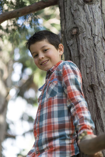Outdoor portrait of a cheerful Young boy Boys Casual Clothing Checked Pattern Child Childhood Emotion Happiness Innocence Leisure Activity Lifestyles Looking At Camera Males  One Person Outdoors Plant Portrait Pre-adolescent Child Real People Smiling Tree Tree Trunk Trunk