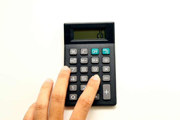 Close-up of hand using calculator against white background