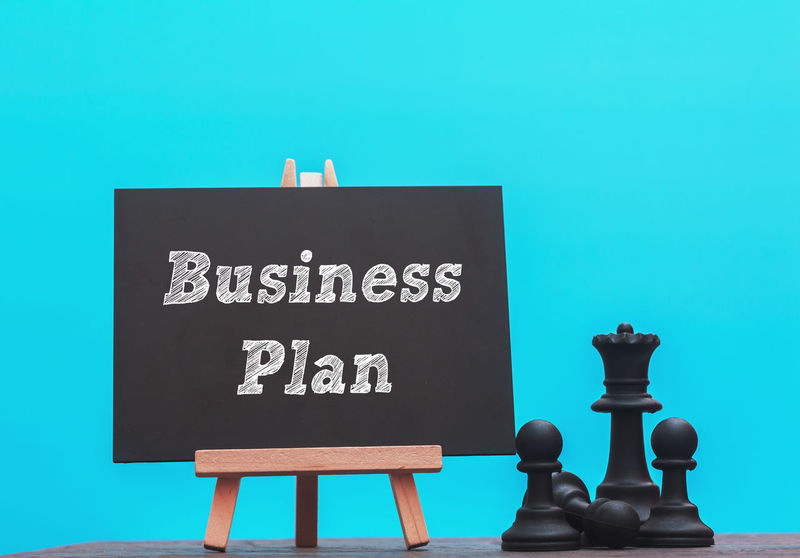 Business Plan word written on blackboard with black chess on blue background Blackboard  Blue Chess Chess Piece Close-up Day No People Outdoors Sky Text