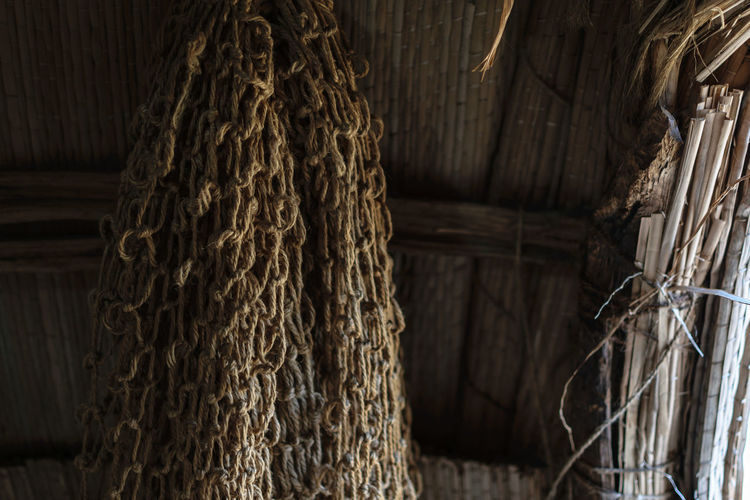 Close-up of rope tied up on wooden wall