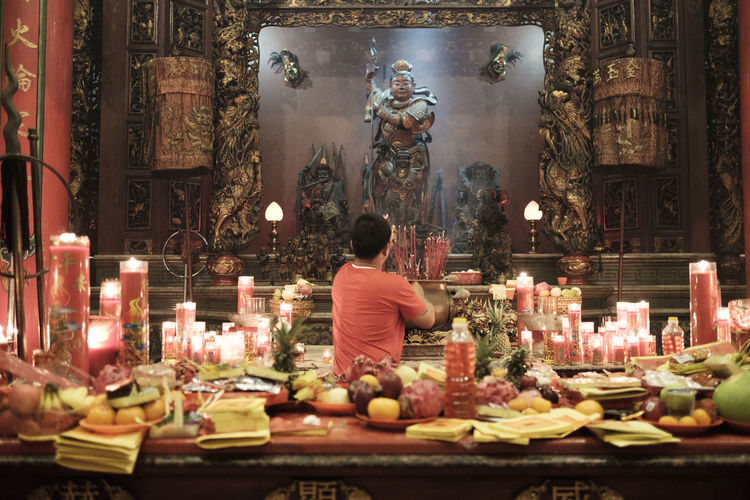 Benoa, Bali, Indonesia - January 28, 2017 : People praying and wishing a happy chinese new year on vihara satya dharma. Altar Architecture Art And Craft Belief Built Structure Burning Candle Fire Flame Human Representation Illuminated Indoors  One Person Place Of Worship Praying Real People Rear View Religion Spirituality Statue