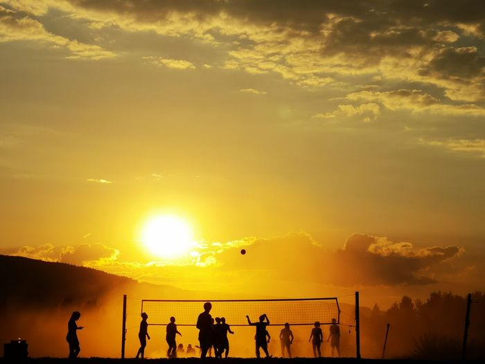 Silhouette of people playing volleyball against sky during sunset