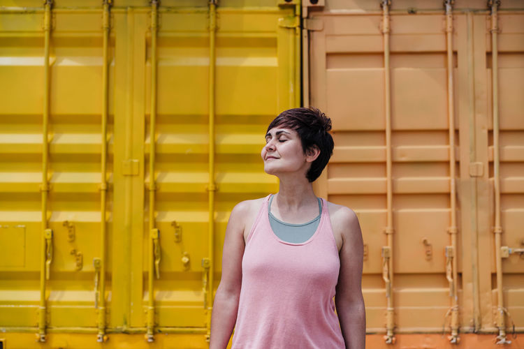 Woman standing against yellow wall