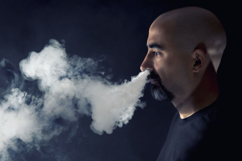 Side View Of Mature Man Smoking Cigarette Against Black Background