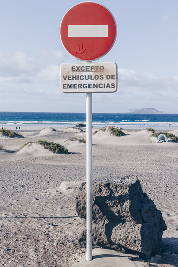 Information sign on road by sea against sky