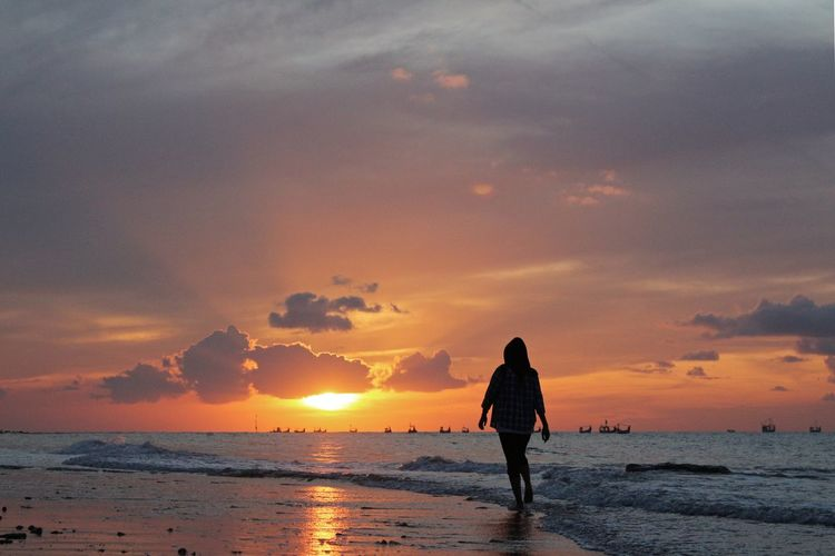 Rear view of woman walking on shore against orange sky