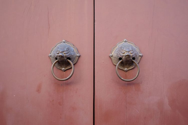Close-up of knockers on closed door