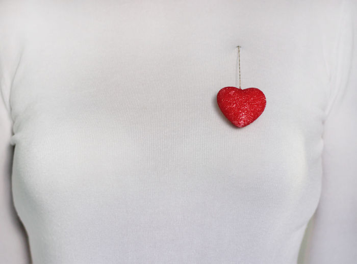 Close-up of woman with heart shape over white background