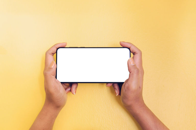 Low section of person holding smart phone against yellow wall