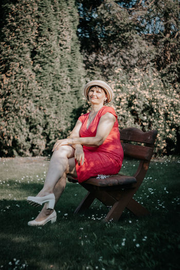 Portrait of mature woman sitting on bench at park