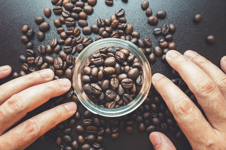 Cropped image of hand holding coffee beans on table