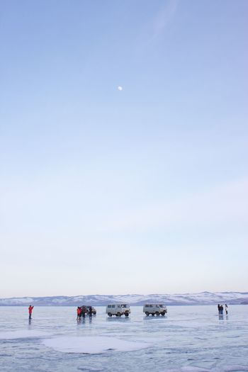 Off-Road Vehicles And People At Frozen Lake Baikal Against Sky At Dusk