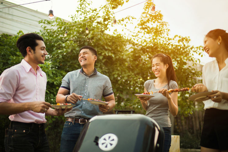 Barbecue Barbecue Grill Casual Clothing Day Emotion Enjoyment Friendship Fun Grilled Group Of People Happiness Leisure Activity Lifestyles Men Nature Outdoors Preparing Food Smiling Standing Three Quarter Length Togetherness Young Adult Young Men