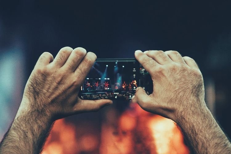 Cropped hand holding smart phone during music concert