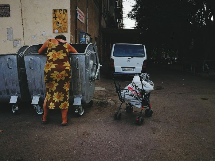 City Outdoors Homeless Homeless Person Rubbish Bins Hardship Full Length Old Woman Old Buildings Hunger Diversity Poor People  Poor  EyeEmNewHere Car Sunflower Dress EyeEm Selects Investing In Quality Of Life The Week On EyeEm