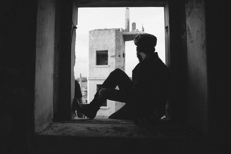 Side view of man sitting on window of abandoned building