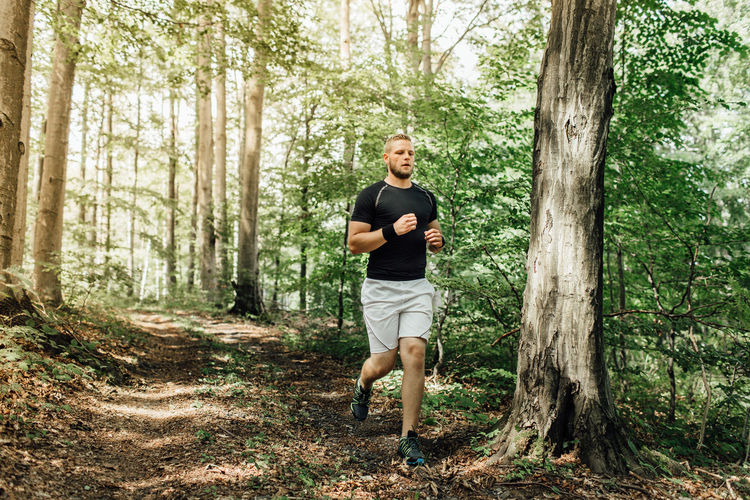 Full Length Of Young Man Running In Forest