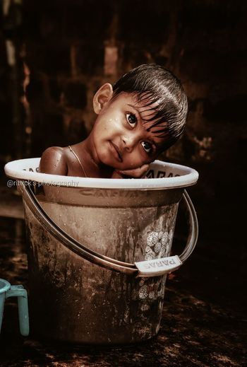Girl looking away while sitting in bucket