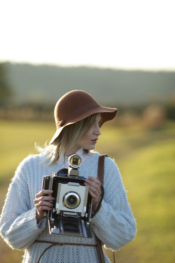 Young woman with camera standing on field