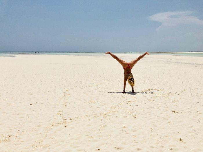 Rear view of young bikini woman doing handstand on sandy beach against sky