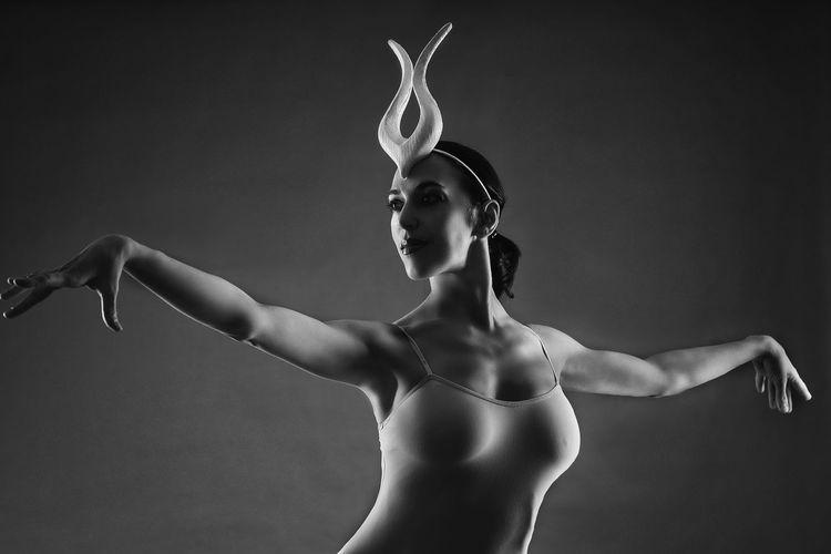 Ballerina dancing against black background